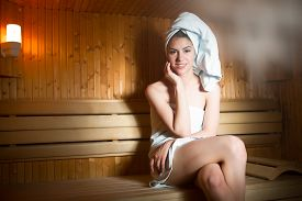 picture of sauna woman  - Pretty young  woman sitting relaxed in a wooden sauna - JPG