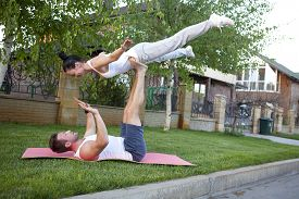 picture of tantra  - An attractive man and woman practice tantra yoga on a grass before the house - JPG