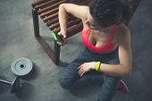 Fitness Woman Sitting In Loft Gym With Cell Phone poster
