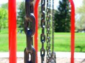 foto of swingset  - A row of swings on a swingset in a park - JPG