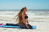 Woman Doing Yoga Exercise On Beach In Salamba Kapotasana Or Supported Pigeon Pose