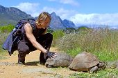Attractive Backpacker Touches Turtle On Road poster