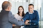 Businessman shaking hand with a young couple in office. Bank agent and his client shaking hands in c poster