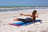 Woman Doing Yoga Exercise On Beach Shalabhasana Or Locust Pose