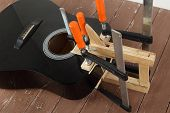 Guitar Repair And Service - Repair Clamping Broken Sound Board Acoustic Guitar Wooden Background poster