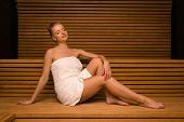 Woman doing a steam bath in a wooden sauna room poster