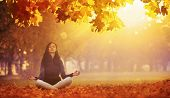 Beautiful Young Woman Meditating Outdoors In Autumn Park. Fall Scene poster