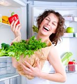 Dieting concept .Diet. Beautiful Young Woman near the Refrigerator with healthy food. Fruits and Veg