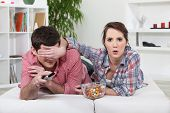stock photo of risque  - Young couple watching television - JPG