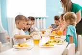 Kids Have A Dinner In Kindergarten. Little Boys And Girls From The Group Of Children Sitting At Tabl poster