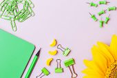 School And Office Stationery On A Pink Background. Green Paper Clips, Green Pencil, Green Notebook,  poster