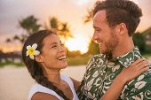 Happy couple lovers in love on romantic sunset beach vacation in Hawaii travel. Asian woman hugging  poster
