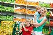 stock photo of grocery-shopping  - woman and child girl with shopping cart in fruit vegeable department of supermarket store - JPG