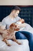 Portrait Of Young Caucasian Father With Mixed Race Asian Chinese Newborn Baby. Dog Pet Lying On Bed. poster