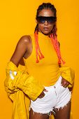 Image of glamour african american woman wearing sunglasses and windcoat posing at camera isolated ov poster