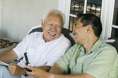 foto of early 60s  - Father and Son Laughing and Using Cell Phone - JPG