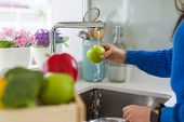 Young woman washing vegetables and fruit using water from sink poster