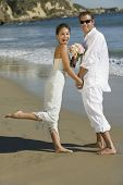 stock photo of early 60s  - Excited Bride and Groom on Beach - JPG