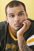 pic of facial piercings  - Young man resting head in hand and thinking - JPG