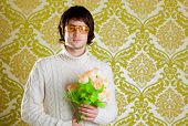 stock photo of dork  - retro hip young man vintage glasses holding valentines flowers bouquet on wallpaper - JPG