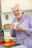 Senior woman preparing food in domestic kitchen poster