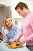 foto of middle-age  - Mature couple preparing meal in domestic kitchen - JPG