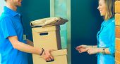 Smiling delivery man in blue uniform delivering parcel box to recipient - courier service concept poster