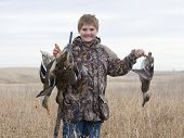 stock photo of duck-hunting  - Boy out duck hunting in the fall in North Dakota - JPG