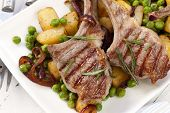 Lamb cutlets served with roasted potatoes, baby peas, and onions.