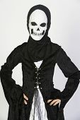 Preteen girl in grim reaper's outfit standing with hands on hip isolated over white background