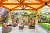 stock photo of red back  - Exterior covered patio with fireplace and furniture - JPG