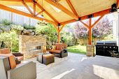 stock photo of grass area  - Exterior covered patio with fireplace and furniture - JPG