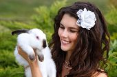 pic of alice wonderland  - Young woman bride smiling and holding two cute rabbits over park summer nature outdoor - JPG