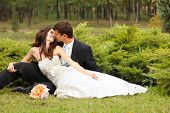 wedding, beautiful young bride lying together with groom in love on green grass kissing, park summer