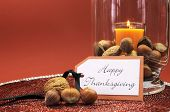 stock photo of happy thanksgiving  - Beautiful Happy Thanksgiving table setting centerpiece with orange candle and nuts in decorative glass hurricane lamp vase and autumn arrangement - JPG