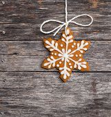 stock photo of ginger bread  - Cute snowflake gingerbread cookie hanging by twine over a rustic wooden background - JPG