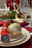 stock photo of christmas meal  - Modern and stylish Christmas dinner table setting including plates glasses and placemats bon bons and Christmas decorations. Red and white table decorated for Christmas Day. Portrait (vertical) orientation. Focus on plates.