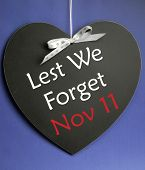 image of veterans  - Lest We Forget message written on heart shape blackboard for Remembrance Day Poppy Day Armistice Day on November 11 - JPG
