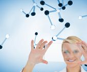 Composite image of doctor holding up clear pane and smiling in front of 3d molecules