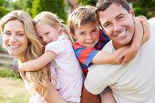 stock photo of boys  - Portrait Of Happy Family In Garden - JPG