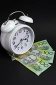 picture of tick tock  - White old fashion alarm clock with Australian hundred dollar notes on black background for time and money concept - JPG