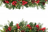 Christmas floral border with holly, ivy, mistletoe, pine cones and winter greenery over white backgr
