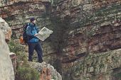 image of wild adventure  - Man with map exploring wilderness on trekking adventure - JPG