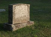 stock photo of funeral home  - A large gravestone in a graveyard shot in the golden light of dusk - JPG