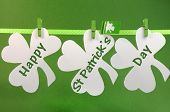 stock photo of shamrocks  - Celebrate St Patricks Day holiday on March 17 with Happy St Patricks Day message greeting written across white shamrocks hanging from pegs on a line against a green background - JPG