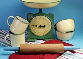 Vintage Kitchen Equipment Including Retro Scales, Yellow And Green Tin Cups And Bowls, Red Oven Glov