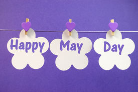 foto of pegging  - Happy May Day greeting message written across white flower cards with purple heart pegs hanging from pegs on a line for May Day May 1 celebration - JPG