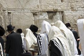 stock photo of israel people  - group of people prays at the western wall in Jerusalem - JPG