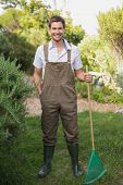 Full length portrait of a young man in dungarees holding rake in the garden