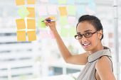 Smiling designer writing on sticky notes on window looking at camera in creative office